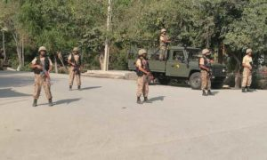 Army soldiers stand guard at street after suicide bombers attacked a Christian neighborhood in Khyber Agency near Peshawar,